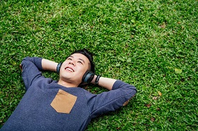 Person laying on the grass listening to headphones